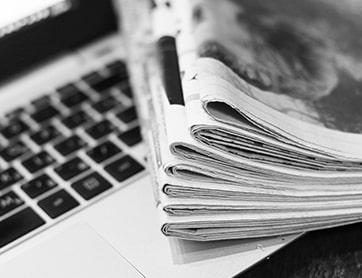 Stapel kranten en toetsenbord